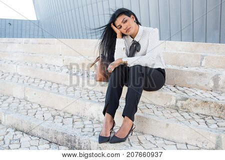 Sad boring businesswoman sitting on stairs and looking away. Unhappy young Hispanic student worried about exam or tired after class. Loneliness concept