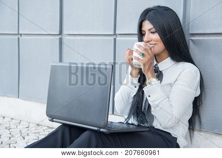 Satisfied pretty woman drinking coffee and working on laptop outdoors. Cheerful young Hispanic businesswoman smiling while reading news on laptop. Business everywhere concept poster
