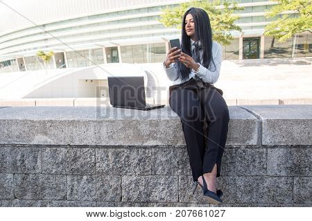 Serious Hispanic businesswoman using devices outdoors while sitting on concrete slab. Beautiful female freelancer taking selfie. Modern business lifestyle concept