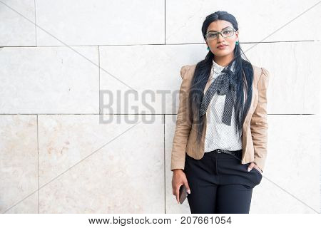 Serious smart stylish businesswoman in jacket looking at camera near wall outdoors. Confident beautiful Hispanic student with smartphone walking after classes. Modern woman concept