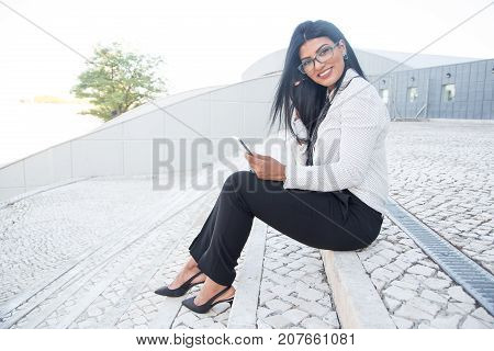 Smiling pretty woman enjoying smartphone opportunity and looking at camera outdoors. Happy young Hispanic business lady using gadget and sitting on step. Work-related technology use concept