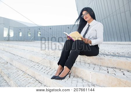 Thoughtful young woman enjoying literature and sitting on stairs in campus. Concentrated Hispanic businesswoman learning management. Business school concept
