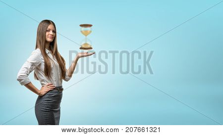 A blond businesswoman stands and holds one hand palm up with a large hourglass hovering above it. Counting time. Never late. Business schedule.