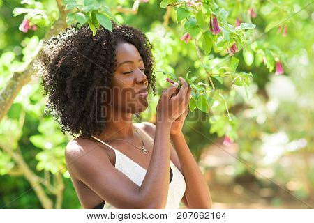 Closeup portrait of smiling young attractive African American woman smelling flowers with her eyes closed and standing in park