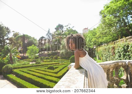Closeup portrait of dreamy young attractive African American woman standing and leaning on stone railing in park with beautiful garden in background. Side view.