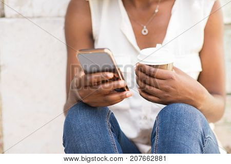 Close-up of female hands holding mobile phone and coffee. Young African-American woman wearing blouse and jeans sitting in street and using smartphone. Communication and leisure concept