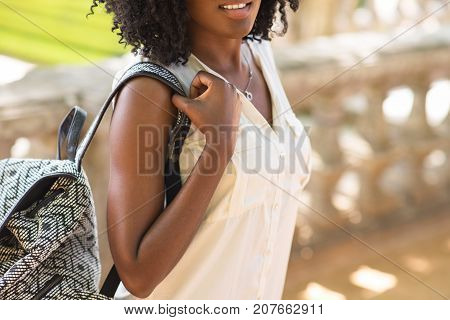 Close-up of confident young African-American woman wearing white blouse and carrying backpack walking and smiling. Recreation and travel concept
