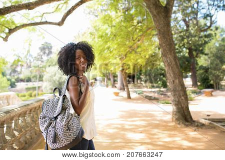 Portrait of happy young African-American woman wearing white blouse and carrying backpack walking in park, looking at camera and smiling. City break and travel concept