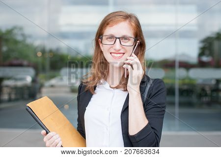 Closeup portrait of smiling young business woman looking at camera, holding file with documents and calling on smartphone with blurred view in background. Front view.
