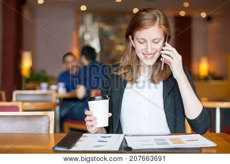 Closeup portrait of smiling attractive young woman working, holding disposable cup, calling on phone and sitting at table in cafe with blurred interior and people in background