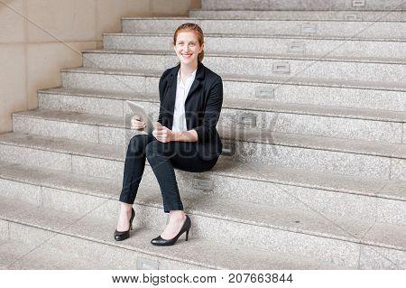 Portrait of smiling attractive young business woman looking at camera, using tablet computer and sitting on stairs outdoors