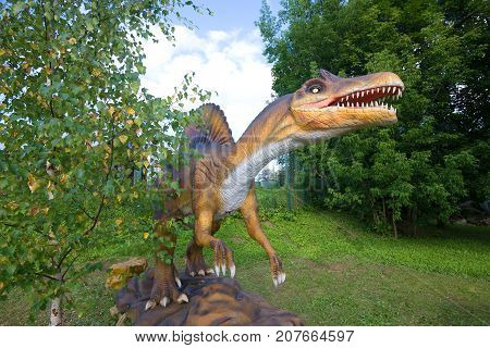 KOTELNICH, RUSSIA - AUGUST 30, 2017: A sculpture of a Spinosaurus in the paleontologic park in the sunny August afternoon