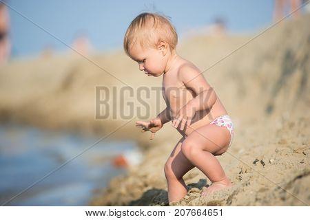Baby playing with toys on the sandy beach near the sea. Cute little kid in  sand on tropical beach. Ocean coast.