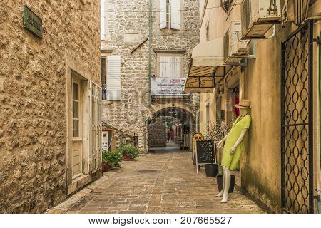 Budva, Montenegro - August 22, 2017: Old Town Street Budva, Montenegro. The first mention of this city - more than 26 centuries ago. We see ancient houses, a very narrow street, cafes, shops.