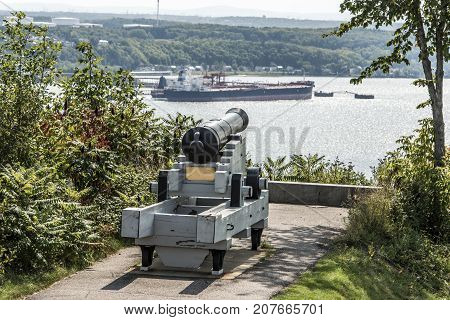 Cannon in Quebec City Canada - plaines Abraham overlooking Saint Lawrence river and Jean-Gaulin Refinery in Levis town
