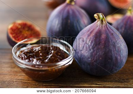 Beautiful ripe purple fig with glass bowl of fig jam on darkwood table