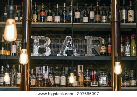 Quebec Canada 13.09.2017 Bitters and liquor bar counter with bottles toned vintage style brick wall and ambient light