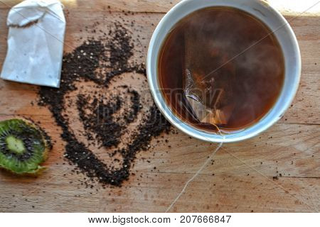 Hot tea in the cup, tea bag, tea powder hearth at the wooden background /top view