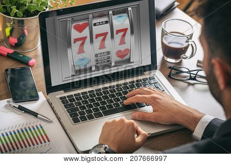 Online gambling concept. Man with a laptop slot machine on the screen office background