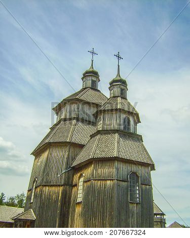 A Church Made Of Wood Stands Against The Blue Sky.
