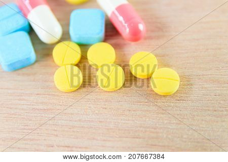 pills yellow On wooden floor with copy space add text ( high definition image )