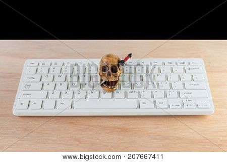 skull on computer keyboard white over wooden floor. halloween concept background with copy space add text ( high definition image )