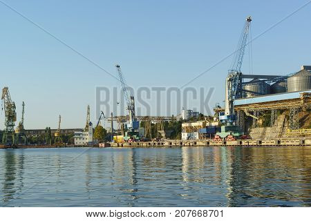A View From The Bay To The Grain Terminal And Loading Cranes Seaport On The Dock. Stevedoring Compan