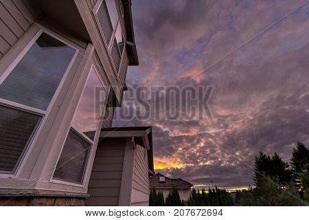 Reflection of sunset sky on windows of suburban neighborhood home in North America