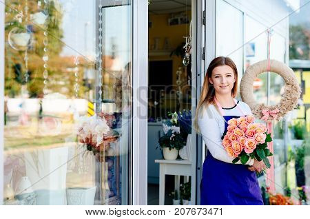 Woman Owner Of Florist Shop With Bunch Of Roses.