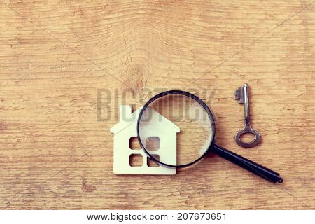 model of the house with a key and a magnifying glass on wooden surface top view / thorough property inspection