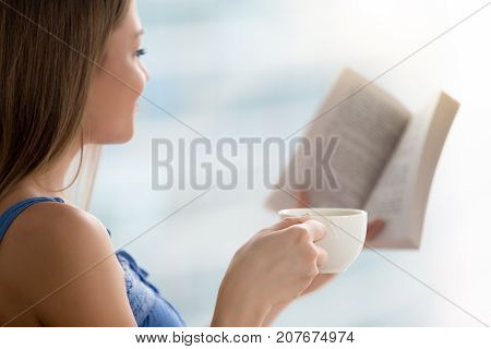 Young woman reading interesting paper book at home while holding cup of coffee in the morning, happy girl enjoying latest new bestseller spending time with literature, romance novel lover, close up