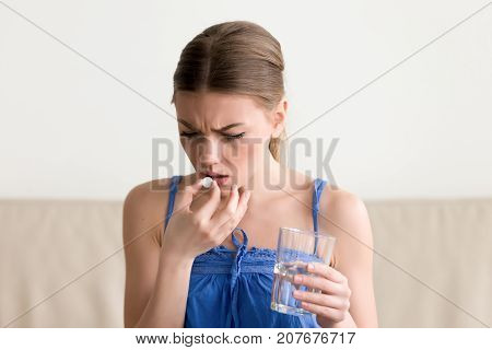 Worried sick young woman holding pill glass of water at home, teen feels ill taking medicine, depressed girl about to take antidepressant pill, emergency contraceptive, painkiller for painful periods