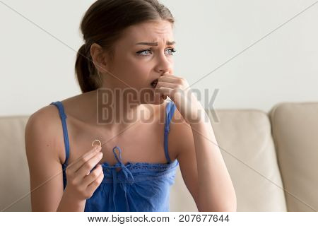 Doubtful young woman holding wedding ring in hand, feeling unsure hesitating about engagement proposal, sad wife thinking about breaking up or getting divorced concept, unhappy marriage