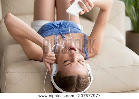 Young woman lying upside down on sofa at home in white headphones, teen girl listening to mp3 music, enjoying favorite radio station, using player app on smartphone, singing along hearing audio track