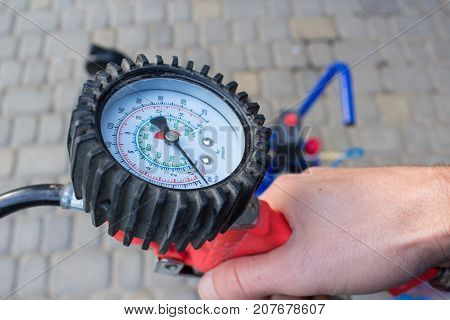 hands hold pressure gauge for measuring automobile pressure