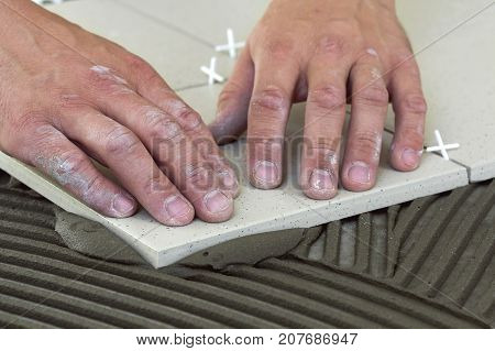 Workers hands with ceramic tiles and tools for tiler. Floor tiles installation. Home improvement renovation - ceramic tile floor adhesive mortar