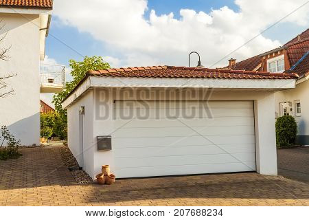 Detached white garage with orange brick tile roof