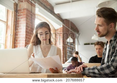 Young female entrepreneur holds paperwork, explains information in documents to coworker. Job supervisor tells intern employee workflow specifics, approving business report, verifying work strategy