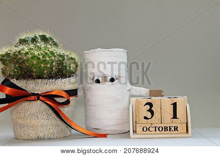 Halloween, celebration or holiday background concept : Halloween paper craft, cube calendar and cactus on gray background