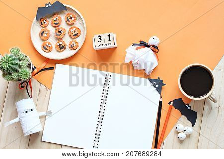 Halloween, celebration or holiday background concept : Mock up of open notebook, paper crafts, cube calendar, grilled carrots with scary face and coffee cup, Top view or flat lay with copy space