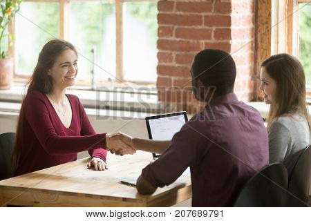 Smiling woman shaking hands with african american HR representative or new coworker. Employees greet each other before meeting, briefing about to start. Job interview or teamwork introduction concept.
