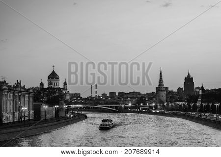 Moscow Russia. Aerial view of popular landmark Kremlin in Moscow Russia at night. Moscow Russia. Cars at the road. Illuminated Kremlin wall and touristic boat at Moscow river. Black and white