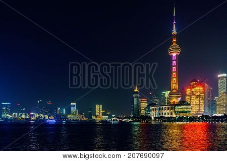 Shanghai, China - Nov 4, 2016: Night view of the Shanghai City skyline. Features the Oriental Pearl TV tower and Huangpu River. Some low-lying haze around.