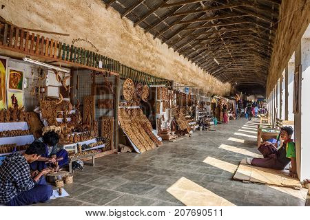 BAGAN, MYANMAR - JANUARY 23, 2016 : Sellers produce and offer souvenirs at the entry of  Shwezigon Pagoda in Nyaung Oo, Bagan, Myanmar