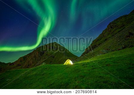 Illuminated tent in the Lofoten islands in Norway with the northern lights overhead.