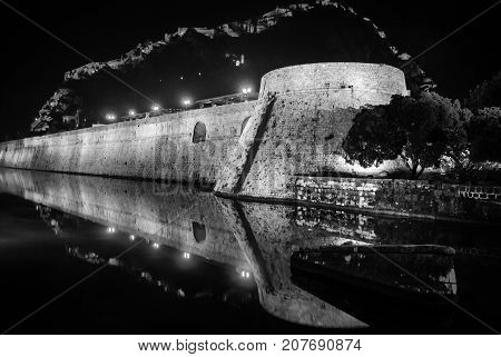 Kotor, Monenegro. Illuminated Old fortress of Kotor, Montenegro at night. Tower and wall, mountain at the background. Fortress wall at the background. Black and white