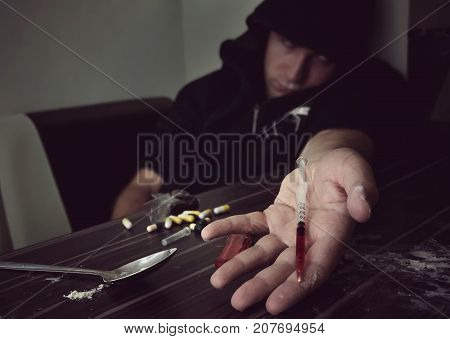 Young Man In Heroine Overdose Holding Syringe