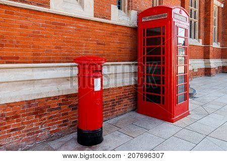 Red Telephone And Post Box In Street With Historical Architecture In England