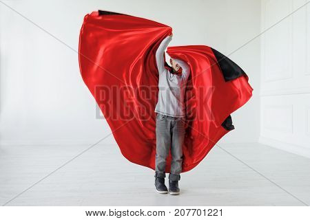 Boy fluttering red vampire cloak at Halloween. Playing boy with Halloween vampire costume fluttering his red, black cloak, in a light space. Smiling kid waiting halloween, copy space available