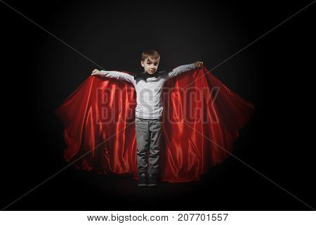 Halloween vampire boy waves his black, red cloak with his hands surrounded by white flying self made balloons ghosts with big black eyes, on black studio background. Kid vampire makeup.